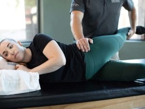 A patient laying on her side on a table with the therapist pressing on her hip.
