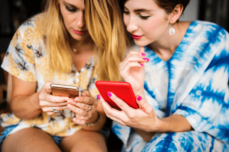 Two women sitting together on looking at their cell phones.